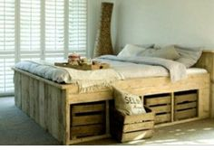 Bed made of pallets. I just love the boxes down the bed. Good for organizing stuff.