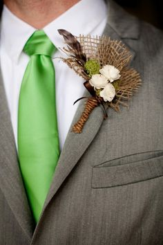 Boutonniere with pheasant or partridge feathers, burlap and some flowers.