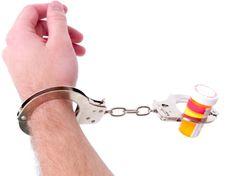 Linke männliche Hand mit Handschelle an orangefarbenes Arzneimittelbehältnis gekettet.