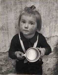 Young girl with a dirty face holding out an empty metal cup, 1949, by Chim (David Seymour)