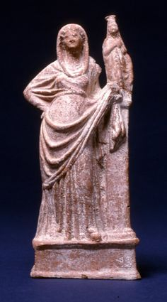 Terracotta figure of a woman leaning against a pillar, wearing chiton and himation which is drawn over her head with loose end falling down by the pillar, archaistic female statue standing on top of pillar, statue dressed in long garment with polos on her head, statue's right hand raised to her breast.  Fine dark red clay (with mica), white coatin, red on shoe, pink on himation.  Excavated/Findspot Myrina (said to be from)  (Asia,Turkey,Myrina)  2ndC BC(late)-1stC BC(early) (circa)…
