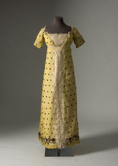 Yellow spotted muslin dress with decorative panel of silk blonde bobbin lace c.1815. Fashion Museum, Bath.