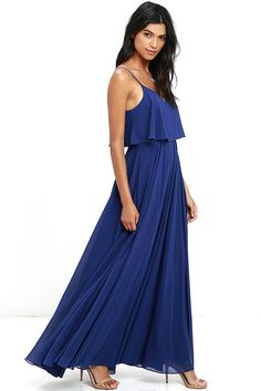 We're absolutely love struck over the Love Runs High Royal Blue Maxi Dress! Royal blue woven poly falls from adjustable straps into a tiered, triangle bodice above a cascading maxi skirt full of volume. Hidden side zipper.