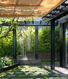 The owners of this shady backyard updated their pergola with a waterfall feature that drips down with a rain-like effect. | Designer: Castanes Architects