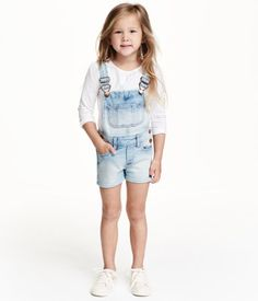 Bib overall shorts in washed stretch denim. Adjustable suspenders with heart-shaped metal fasteners. Bib pocket, side pockets, and back pockets. Snap fasteners at sides.