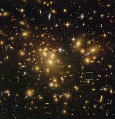 This spectacular view from the NASA/ESA Hubble Space Telescope shows the rich galaxy cluster Abell 1689. The huge concentration of mass bends light coming from more distant objects and can increase their total apparent brightness and make them visible. One such object, A1689-zD1, is located in the box — although it is still so faint that it is barely seen in this picture. New observations with ALMA and ESO's VLT have revealed that this object is a dusty galaxy seen when the universe was just…