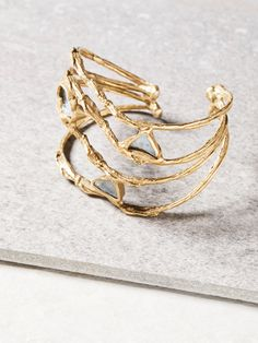 Daybreak Raw Stone Cuff | **Emilie Shapiro**    Handmade in the USA, this beautiful brass cuff features stunning Aquamarine stones embedded throughout.