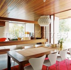 Openplan dining and living area in 70s house with tongue and groove wood panelled ceiling and Le Klint lightshade