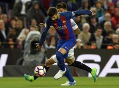 Barcelona's defender Gerard Pique (front) vies with Sevilla's Argentinian midfielder Joaquin Correa during the Spanish league football match FC Barcelona vs Sevilla FC at the Camp Nou stadium in Barcelona on April 5, 2017. / AFP PHOTO / LLUIS GENE