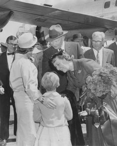 FILE-Teacher Barbara Brewster and 9-year-old Patricia Gail Sheppard offer Mamie Eisenhower a bouquet after the Eisenhowers' arrival in Augusta on April 11, 1960.