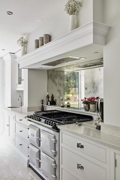 Luxury Kitchens This Aga range cooker mixes classic design with the convenience of a gas hob and electric oven. - This contemporary grey kitchen features high quality silestone worktops as well as state of the art Neff and Miele appliances. Antique Mirror Splashback, Mirror Backsplash Kitchen, Kitchen Mantle, Aga Kitchen, Kitchen Cooker, Open Plan Kitchen Diner, Home Decor Kitchen, Kitchen Interior, Antiqued Mirror