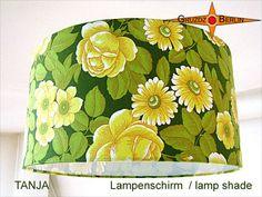 Erfrischend wirkt dieser Lampenschirm in trendigem Format:  Der **Lampenschirm TANJA** mit gelben Blüten auf grünem Untergrund.  Der Schirm ist einsetzbar für Pendelleuchten, für Steh- und...