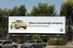 "Volkswagen billboard. ""Misery has enough company. Dare to be happy."""