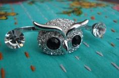 Anel duplo em metal prata no formato de coruja com um cristal Swarovski de cada lado. Aplicação de strass branco e preto na coruja.  Aros 20 (diâmetro: 1,85cm) e 21 (diâmetro: 1,88cm) R$52,00