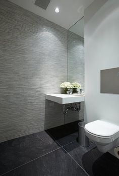 Modern bathroom gray looks like wall paper all up wall with black flooring.