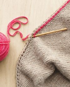 Crochet a chain of slip stitch through a YO edging for a firm, tailored edge - in a contrast color or the same color.