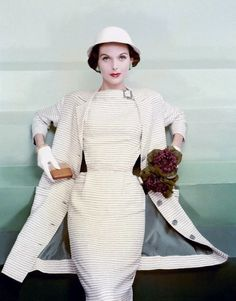 January 1955 Anne is wearing a wasp waist, blue on white striped linen dress with a matching coat and a round white linen hat.