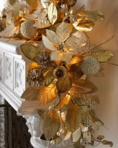 A glorious gold and white garland decorates the mantel for the holidays!!! Bebe'!!! Garland of white silk poinsettias and gold leaves with clear twinkle lights!!!