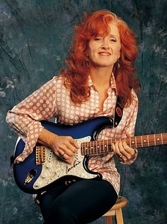 """is an American blues singer-songwriter and slide guitar player. During the 1970s, Raitt released a series of roots-influenced albums which incorporated elements of blues, rock, folk and country. In the 1990s she had a major return to form with the release of her album """"Nick of Time"""" after several years of critical acclaim but little commercial success."""