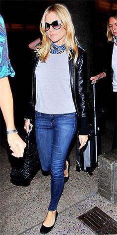 Sienna Miller in a grey top, black leather jacket, skinny jeans and black flats.