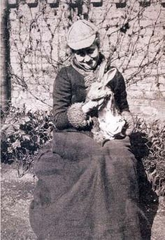 Beatrix Potter, seated, holding a rabbit