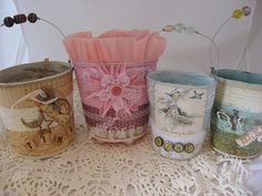 Squish old tin cans to this shape- then decoupage, paint, add  beads and a, wire handle.