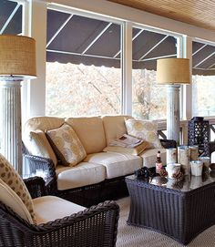 A wicker set by Summer Classics provides seating on the screened side-porch in this Tennessee home. Cast-off columns were repurposed as floor lamps.   - HouseBeautiful.com