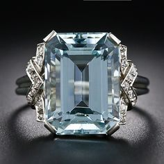 A light pastel-blue emerald-cut aquamarine, weighing 8.00 carats, glistens and gleams and is embraced left and right with a geometric design of twinkling single-cut diamonds in this quintessentially Art Deco bauble - circa 1930s-1940s. The chevron motif on each side leads to a sleekly fluted ring shank.