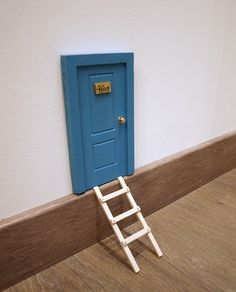 Puerta para el ratoncito Pérez de color azul turquesa. Puerta para el ratón Pérez clásica con placa de metal y escalera de madera.