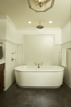 Love the pearl like tiling behind the tub and notice the shower head in the ceiling