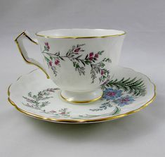 Gorgeous tea cup made by Aynsley. Cup and Saucer both have blue flowers. Gold trimming on cup and saucer edges, as well as on angular handle. Excellent condition (see photos). Markings read: Est 1775 Aynsley England Bone China 27 For more Aynsley tea cups, please click here: