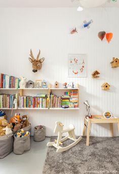 Quarto infantil tem parede com lambris de madeira e estante branca.