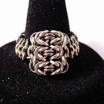 """By hand-weaving almost 200 super-tiny jump rings (1-2mm diameter), this beautiful mesh ring features 3 """"byzantine"""" chainmaille units, connected to a european 4-1 band that forms the rest of the ring. Amazingly comfortable to wear. Available in two different designs: silver, and silver with dark accents. SIZES (approximate"""