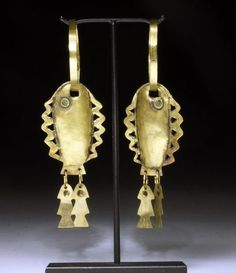 Northern Peru | Chavin high karat gold earrings in the form of a fish.  turquoise eyes |  Ca 900 to 600 BCE | 5,500 - 10,000$
