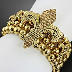 NEW! BEAUTIFUL CRYSTALS AND GOLD TONE  FLEUR DE LIS  STRETCH BRACELET.