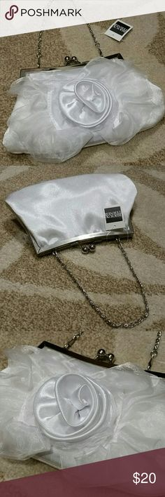 """Bijoux Terner Evening Clutch Purse NWT Bijoux Terner Boutique Evening Clutch Purse. This silky white evening clutch purse features a large silken flower, silver hardware and a short metal chain. This dainty bag has enough room for your phone, money and a couple small personal items. One small interior pocket for ID or credit card. New with tags!  5"""" Tall, 9"""" long base, 6"""" top length Bijoux Terner Boutique Bags Clutches & Wristlets"""