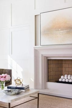 Alyssa Rosenheck- Laurel Powell - Gorgeous living room features a wall fitted with hidden cabinets accented with wainscoting trim flanking a limestone fireplace and a gray and gold abstract art piece.