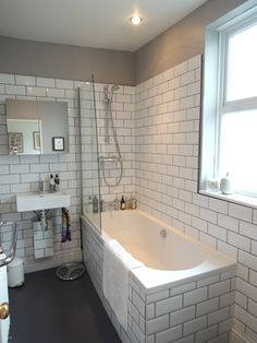 @Nicole Renner Beehler  Brick tiles, dark grout bathroom, grey vinyl flooring, glass shower shield