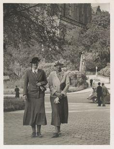 Princesa Tatiana Constantinovna e da princesa Vera Constantinovna, em 1935. Elas estão caminhando juntas em um parque, com a Princesa Tatiana para a direita. Há um grande edifício de pedra, árvores e uma série de outras pessoas por trás delas.