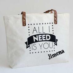 """Bolso de lona grande con mensaje de amor """"All I need is you"""". Un regalo divertido para tu media naranja. Lo personalizamos en el momento con el nombre que quieras. Medidas: 48cm x 35cm."""