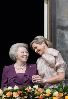 Queen Maxima of the Netherlands (R) talks with Princess Beatrix of the Netherlands as they greet the crowd gathered on Dam Square from the balcony of the Royal Palace in Amsterdam, following the official abdication of Queen Beatrix
