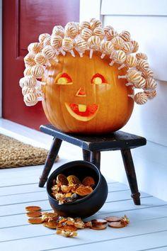 como hacer una calabaza de Halloween, calabaza tallada con cabeza de chupachups sobre silla