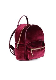 An adorable tiny backpack featuring a velvet exterior and leather straps. Straps are adjustable f...