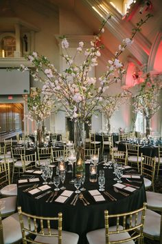 The reception centerpieces featuring flowering cherry blossom branches.   	Venue: Ashford Estate  	Floral Design: WaterLily Designs