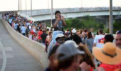 Fourteen-year-old Talana Green, of Charleston, documents the massive crowd streaming from E. Bay Street onto the bridge toward Mount Pleasant.