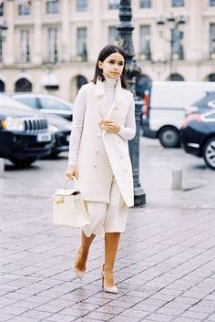 A white turtleneck top is worn with white culottes, a white sleeveless coat, white structured bag and nude pointed toe heels.