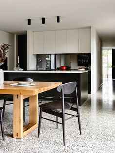 Kitchen/dining: polished concrete floor, matt white handleless cabinets, black island, tinted mirror splashback, white stone benchtop, wooden rectangular dining table, black wooden dining chairs, black surface-mounted halogen downlights