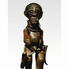 A Superb and Highly Important Songye Community Power Figure the male figure .., wearing a fibre belt with a wooden club and an antelope horn .. a magical charge behind sheeted tin, with necklaces J height 35 in. 88.9 cm Collected in situ by Gaston Heenen, Governor of Katanga, before 1937