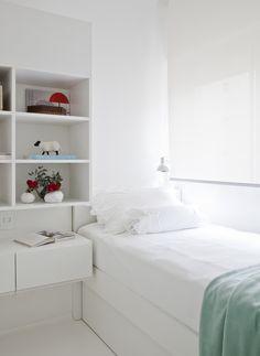 Quarto todo branco e minimalista. Marcenaria branca - cama, prateleiras e criado mudo. Piso de epóxi branco e paredes brancas. Luminária da Reka.