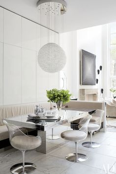In the kitchen dining area of a home decorated by Delphine Krakoff, a large pendant light hangs over a mirrored table and chic clear chairs.